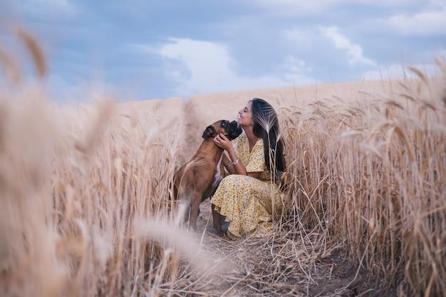 Jonge gelukkige vrouw die haar hond aait terwijl ze samen geniet van de natuur in een tarweveld. natuur en dieren concept.