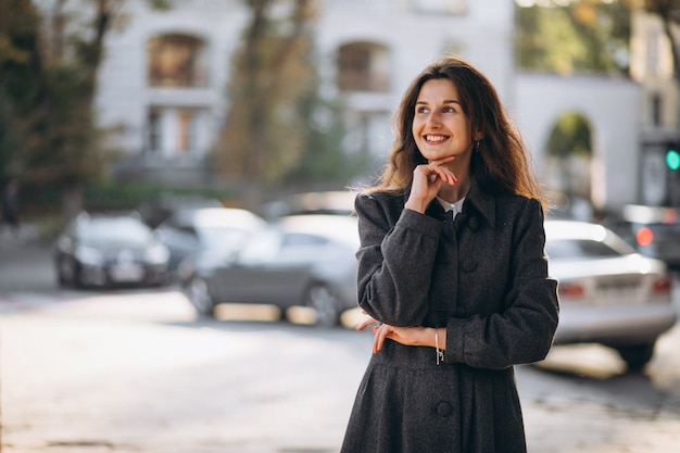 Jonge gelukkige vrouw die in de straat loopt