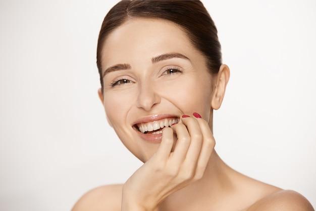 Jonge gelukkige vrouw die lacht geïsoleerd op wit, prachtige vrouw met naakt make-up en perfecte glimlach, schoonheid en cosmetologie stomatologie concept