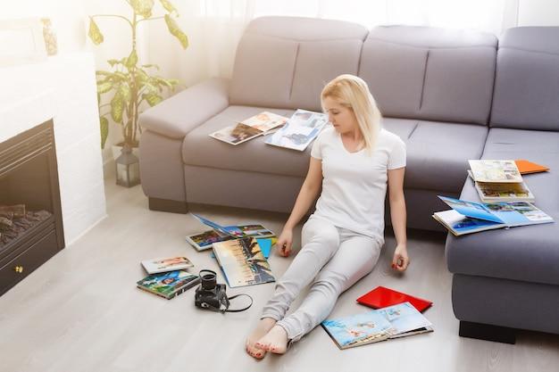 Jonge gelukkige vrouw die naar een fotoboek in haar kamer kijkt