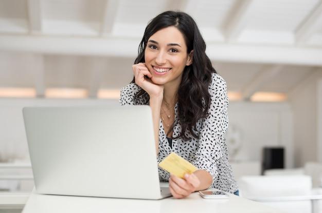 Jonge gelukkige vrouw die online winkelen met haar laptop thuis doet