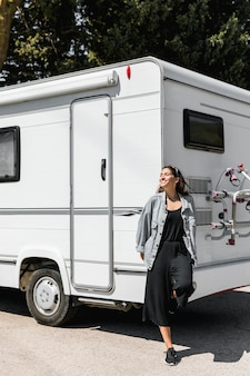 Jonge gelukkige vrouw die op caravan leunt
