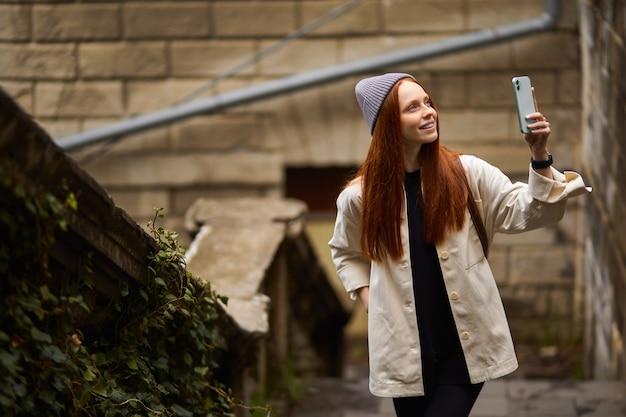 Jonge gelukkige vrouw die op historische plek loopt en foto's maakt op smartphone met behulp van mobiele telefoonportretten...