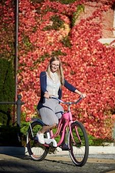 Jonge gelukkige vrouw die roze damefiets cirkelen op heldere warme zonnige dag op achtergrond van bakstenen muur die met mooie rode klimopbladeren wordt overwoekerd.