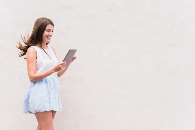 Jonge gelukkige vrouw die tablet bekijkt