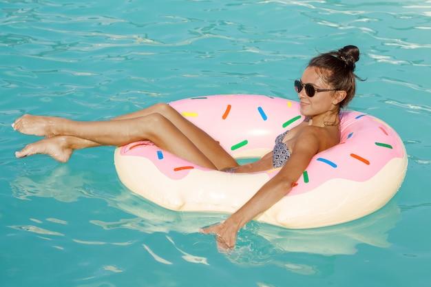 Jonge gelukkige vrouw die van dag genieten bij de pool die op opblaasbare doughnut zwemmen
