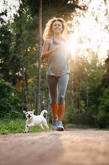 Jonge gelukkige vrouw doet gewichtsverlies fitness in het park met haar hond jack russell