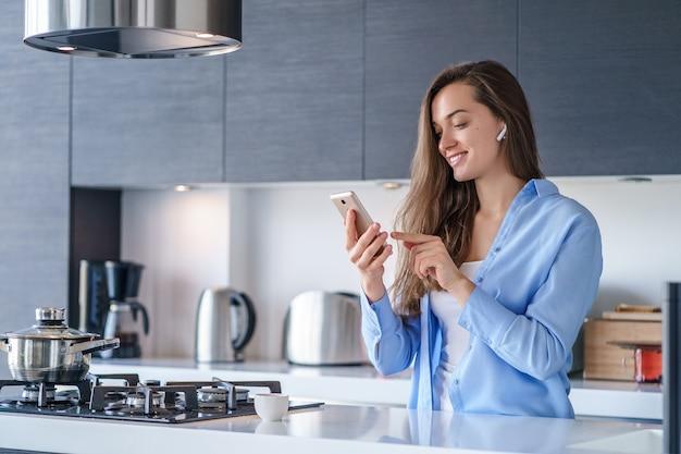Jonge gelukkige vrouw gebruikend smartphone en draadloze hoofdtelefoons voor het luisteren van muziek en het maken van videogesprekken in de keuken thuis. moderne mobiele mensen