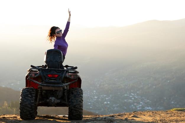 Jonge gelukkige vrouw genieten van extreme rit op quad quad motor in herfst bergen bij zonsondergang.