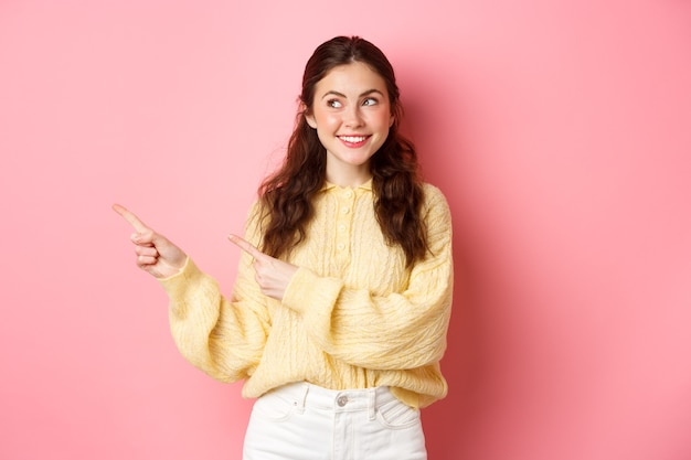 Jonge gelukkige vrouw glimlachend, wijzend en opzij kijkend naar linker copyspace, reclame tonen, staande tegen roze lentemuur.
