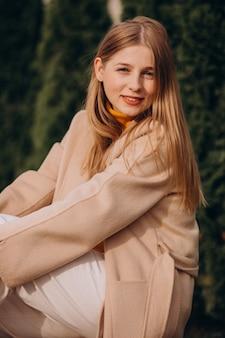 Jonge gelukkige vrouw in beige jas