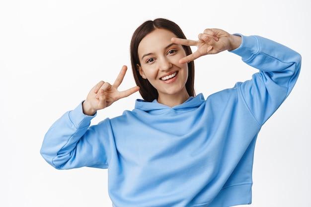 Jonge gelukkige vrouw in blauwe hoodie, vrede v-tekens tonen, disco gebaar in de buurt van ogen, dansen en vrolijk glimlachen, staande over witte muur