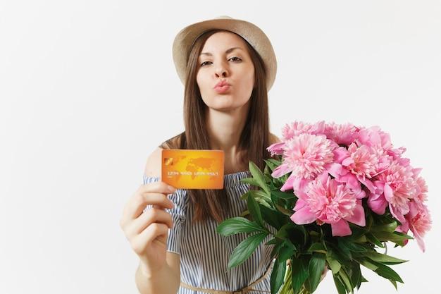 Jonge gelukkige vrouw in blauwe jurk, hoed met creditcard, geld, boeket van mooie roze pioenrozen bloemen geïsoleerd op een witte achtergrond. zaken, levering, online winkelconcept. ruimte kopiëren.