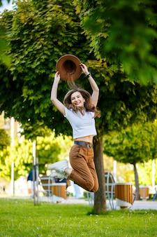 Jonge gelukkige vrouw in een hoed loopt langs een steegje in een park. een meisje met een europese uitstraling met een glimlach op haar gezicht op een zonnige zomerdag
