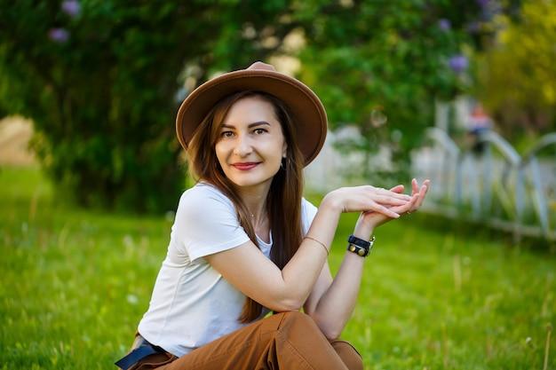 Jonge gelukkige vrouw in een hoed zit op een groen gazon in een park. een meisje met een europese uitstraling met een glimlach op haar gezicht op een zonnige zomerdag