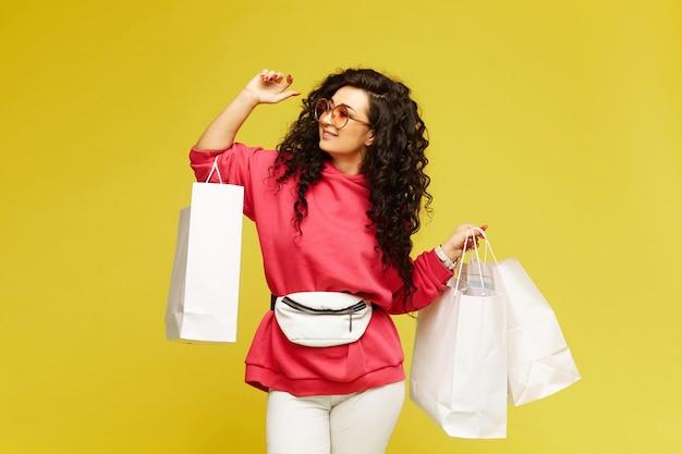 Jonge gelukkige vrouw in een roze hoodie en modieuze zonnebril poseren met boodschappentassen op gele achtergrond, geïsoleerd met kopie ruimte