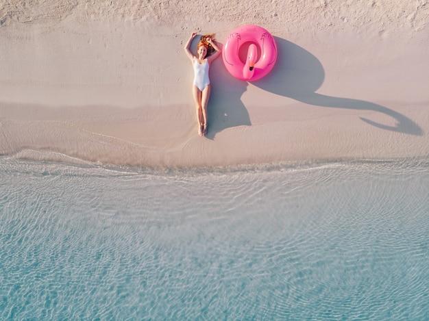 Jonge gelukkige vrouw in een zwembroek ligt in de buurt van een opblaasbare flamingo op het strand, van bovenaf bekeken.