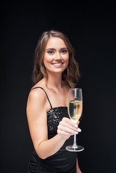 Jonge gelukkige vrouw in elegante jurk met glas champagne op feestje.