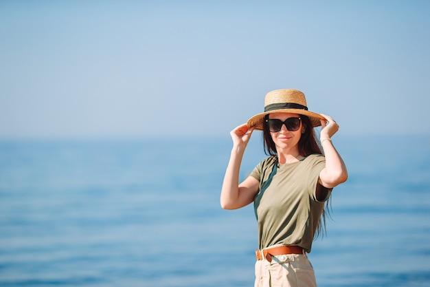 Jonge gelukkige vrouw in hoed op wit strand
