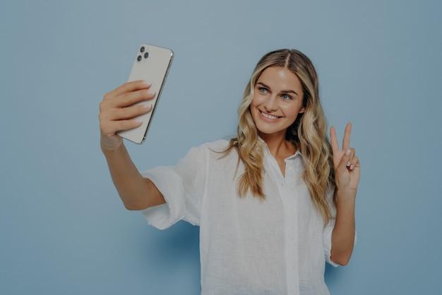Jonge gelukkige vrouw in vrijetijdskleding die selfie neemt terwijl ze vredesgebaar toont met haar hand, glimlachend met brede glimlach voor volgers en zichzelf uitdrukkend, geïsoleerd over blauwe muur