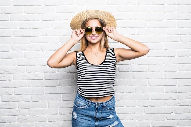 Jonge gelukkige vrouw lachend in zonnebril en zomerhoed over witte bakstenen muur