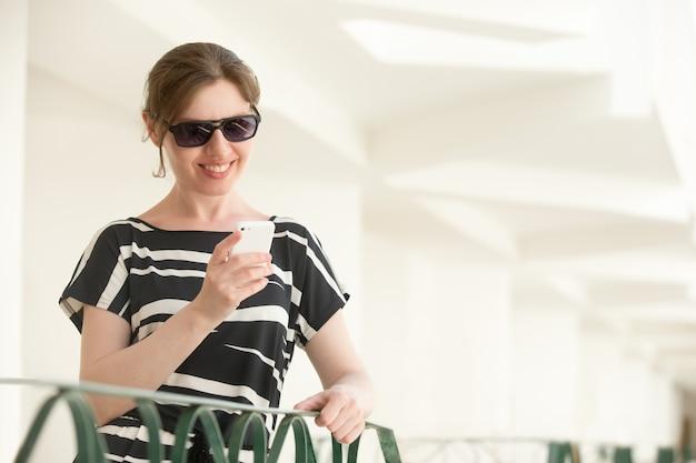 Jonge gelukkige vrouw met behulp van mobiele telefoon op de telefoon