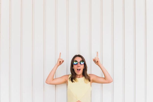 Jonge gelukkige vrouw met duimen die omhoog op witte achtergrond stellen