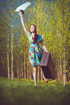 Jonge gelukkige vrouw met een koffer en een kaart die met een hand naar iemand zwaait