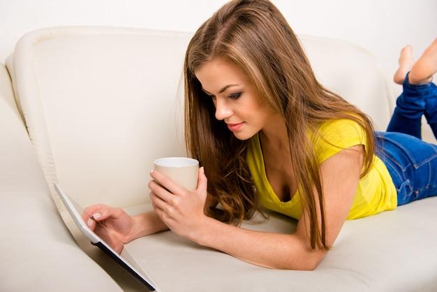 Jonge gelukkige vrouw met een tablet die van de kopholding op de bank ligt