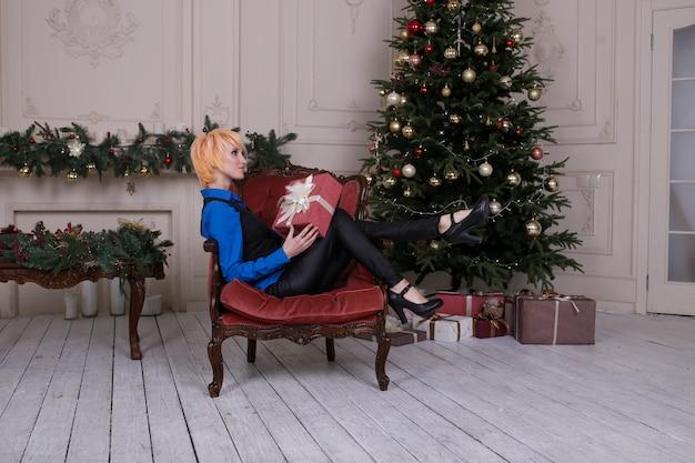 Jonge gelukkige vrouw met geschenkdoos zit in een fauteuil in de buurt van de kerstboom, nieuwjaar
