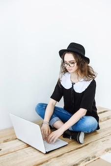 Jonge gelukkige vrouw met hoed en bril werkt op een laptop terwijl ze op een tafel in een witte kamer zit