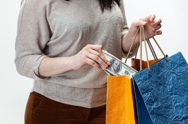 Jonge gelukkige vrouw met in hand dollarsrekeningen.