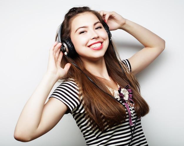 Jonge gelukkige vrouw met koptelefoon luisteren muziek op grijs