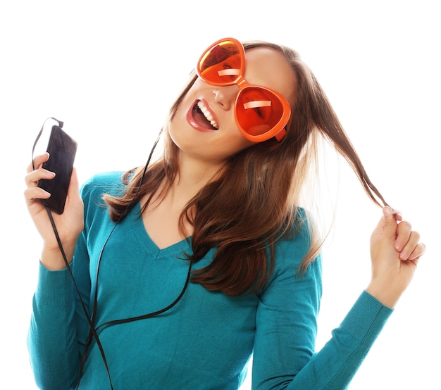 Jonge gelukkige vrouw met koptelefoon luisteren muziek op wit
