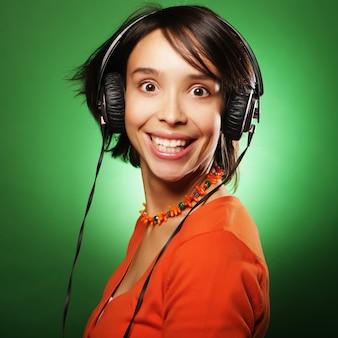 Jonge gelukkige vrouw met koptelefoon luisteren muziek