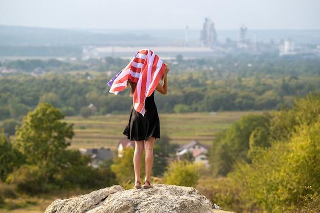 Jonge gelukkige vrouw met lang haar die omhoog zwaait op de wind van de amerikaanse nationale vlag in haar handen die op een hoge rotsachtige heuvel staat en geniet van een warme zomerdag.
