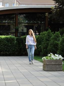 Jonge gelukkige vrouw met lang haar in jeans en shirt loopt door de straat naast groen hek