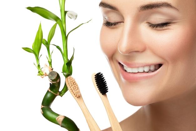 Jonge gelukkige vrouw met milieuvriendelijke bamboetandenborstels