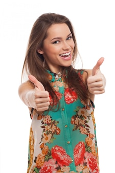 Jonge gelukkige vrouw met omhoog duimen