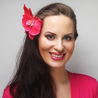 Jonge gelukkige vrouw met roze bloem in het haar