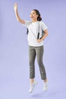 Jonge gelukkige vrouw met rugzak springen en vieren van succes geïsoleerd op een paarse achtergrond