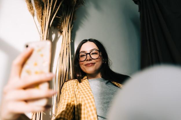 Jonge gelukkige vrouw met smartphone kijken op cel met behulp van mobiele telefoon