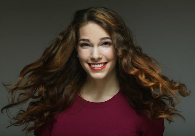 Jonge gelukkige vrouw met wind in haar