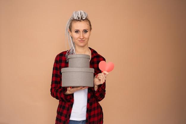 Jonge gelukkige vrouw op valentijn dag met rood hart valentijnskaart en geschenkdozen geïsoleerd op beige achtergrond
