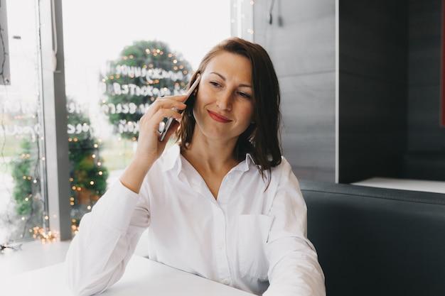 Jonge gelukkige vrouw praten op een mobiele telefoon in een coffeeshop, een dame met een mooie glimlach praten op een mobiele telefoon zittend in een café tijdens de lunch