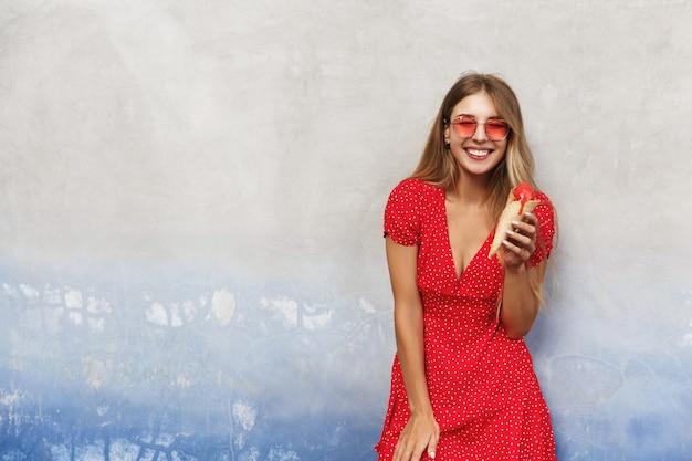 Jonge gelukkige vrouw reizen, zoet ijs eten op zomervakantie, leunen op de muur