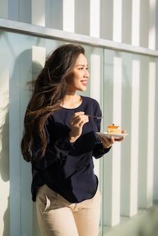 Jonge gelukkige vrouw staat 's ochtends op het terras van het hotel met schotelcake. vrij aziatisch meisje in een goed humeur en is klaar voor avonturen.