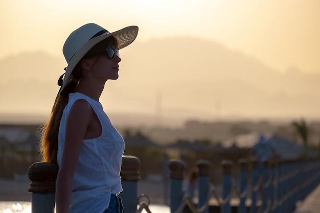 Jonge gelukkige vrouw toeristische ontspannen buiten op warme zonnige avond aan zee. zomervakanties en reizen concept.