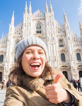 Jonge gelukkige vrouw touris selfie foto maken voor de beroemde duomo kathedraal in milaan