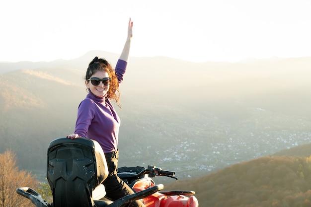 Jonge gelukkige vrouwelijke bestuurder geniet van extreme rit op atv quad-motor in herfstbergen bij zonsondergang